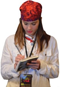 girl student backstage in costume with a red bandana on her head