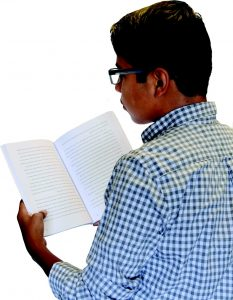 boy in blue and white plaid shirt with glasses reading