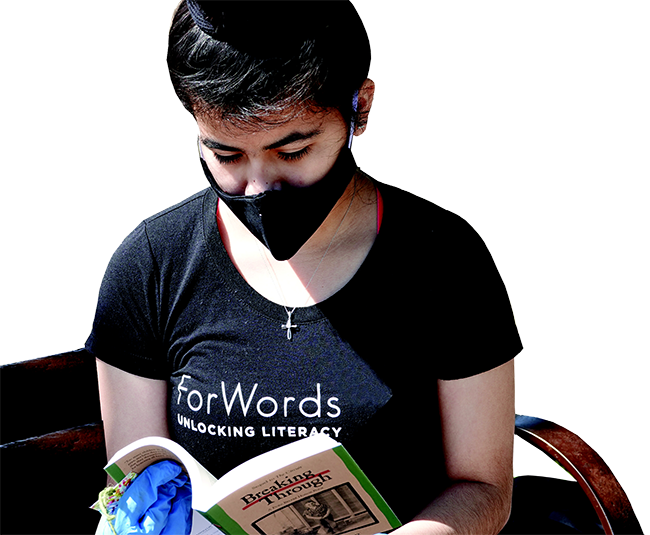 student in black forwords t-shirt wearing mask and gloves reading a book